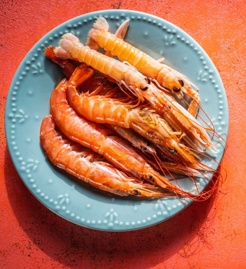 Raw srimps seafood in a blue dish on coral color board