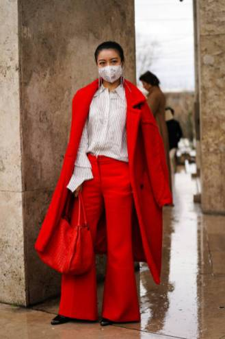 PARIS, FRANCE - MARCH 02: A guest wears earrings, a white shirt with thin black stripes, a red oversized coat, red flare pants, black shoes with a steel tip, a red woven leather large bag, outside Akris, during Paris Fashion Week - Womenswear Fall/Winter 2020/2021, on March 02, 2020 in Paris, France. (Photo by Edward Berthelot/Getty Images)