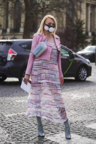 PARIS, FRANCE - MARCH 03: A guest wears a face mask with embroidered white flowers, a pale blue Chanel quilted bag, a pink jacket a flowing ruffled dress with printed geometric patterns, pointy boots, outside Chanel, during Paris Fashion Week - Womenswear Fall/Winter 2020/2021 on March 03, 2020 in Paris, France. Due to a sharp increase in the number of cases of coronavirus (COVID-19) declared in Paris and throughout France, several sporting, cultural and festive events have been postponed or canceled. The epidemic has exceeded 3200 dead for more than 92000 infections in sixty countries. In France, 285 cases are now confirmed and four people died in 13 regions in total. To cope, the French government will requisition the stocks of protective masks by means of a decree published on Thursday. (Photo by Edward Berthelot/Getty Images)