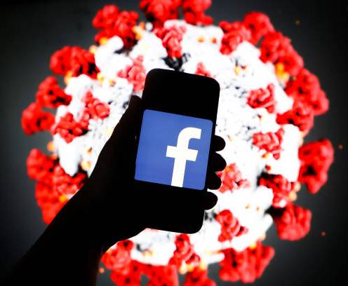 Facebook logo is displayed on a mobile phone screen photographed on SARS-CoV-2 illustration graphic background. Krakow, Poland on 11th March, 2020. (Photo Illustration by Beata Zawrzel/NurPhoto via Getty Images)