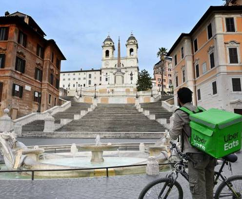 An Uber Eats delivery man stands by the Spanish Steps at a deserted Piazza di Spagna in central Rome on March 12, 2020, as Italy shut all stores except for pharmacies and food shops in a desperate bid to halt the spread of a coronavirus. (Photo by Alberto PIZZOLI / AFP) (Photo by ALBERTO PIZZOLI/AFP via Getty Images)