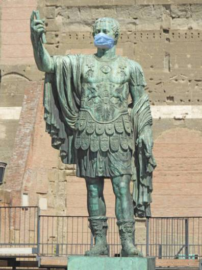 Statue of Emperor Caesar in the empty streets of Rome for quarantine and wearing a surgical mask, due to the world coronavirus pandemic Statues are archaeological remains that are exposed by the streets of Rome