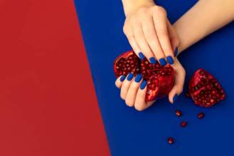 blue manicure on red blue background with pomegranate fruit in hands
