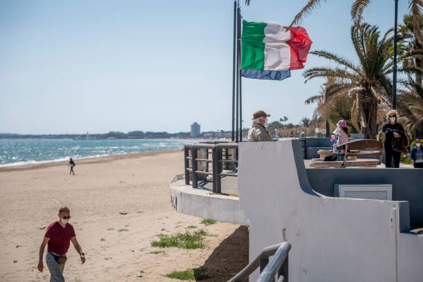 TERRACINA, ITALY - MAY 07: People wearing protective masks walk on an empty beach about 100 km (80 miles) south of Rome during the third day of the so called phase two due to the Coronavirus (Covid-19) pandemic, on May 7, 2020 in Terracina, Italy. Italy was the first country to impose a nationwide lockdown to stem the transmission of the Coronavirus (Covid-19), and its restaurants, theaters and many other businesses remain closed. (Photo by Antonio Masiello/Getty Images)