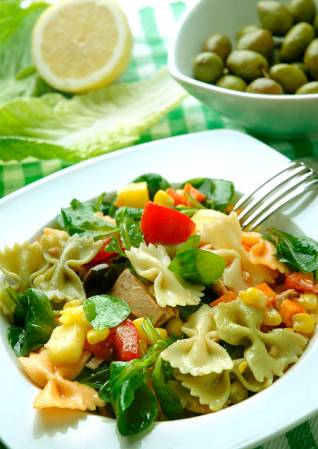 Pasta salad in a white dish, with olives and lemon in te background.