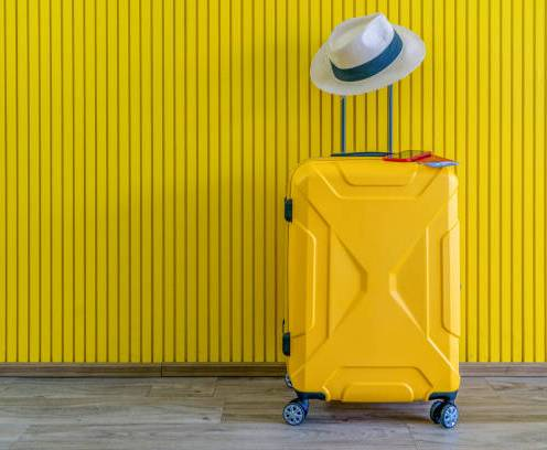 Yellow suitcase with sun glasses and hat on yellow background. travel concept. minimal style