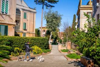 Rome, Italy, February 20 -- A woman walks with her dogs in the Garbatella Quarter, a sector in the Ostiense district of Rome. The Garbatella quarter was built starting from 1920 with a series of areas built for popular use and managed as small communities, with gardens, public areas for recreational use, squares and numerous green areas, with a particular architecture that often recalled the style of the ancients medieval Italian villages. According to the English newspaper The Guardian, this district of Ostiense in Rome is one of the 10 coolest neighborhoods in Europe, with dozens of trendy restaurants, museums and industrial areas recovered. Image in HD format.
