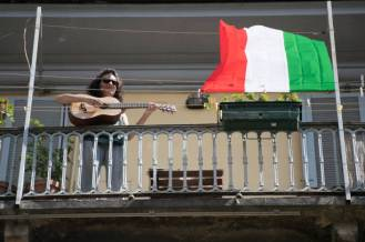 """TURIN, ITALY - APRIL 25: A woman plays a guitar during the flashmob on April 25, 2020 in Turin, Italy. Flashmob """"Bella Ciao"""" people sing the song Bella Ciao from the balconies during the flashmob for Liberation Day. Italy's annual Liberation Day is a national holiday celebrating the official end of Nazi occupation during the Second World War on April 25, 1945. Italy is celebrating the 75th anniversary of occasion in lockdown, which is in place until at least May 4 to stem the transmission of the Coronavirus (Covid-19). (Photo by Stefano Guidi/Getty Images)"""