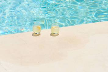 Two nondescript drinks with a lemon garnish sat by the edge of a pool.