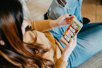Young adult woman ordering some food online for dinner. She's sitting on the sofa at home. Graphic of a food delivery website on the mobile phone.