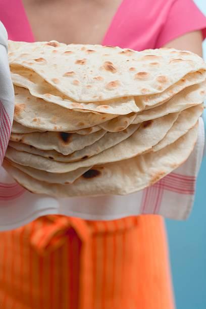 Woman holding freshly baked tortillas on tea towel