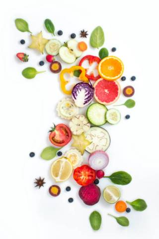 Various colourful vegetables and fruits sliced elements on white background.