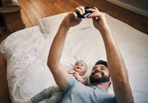 High angle shot of an affectionate young father taking selfies with his little baby girl while lying on a bed at home