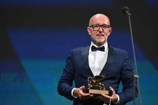 """TOPSHOT - Disney's Marketing Director for Italy, Davide Romani acknowledges receiving the Golden Lion for Best Film on behalf of US director Chloe Zhao for """"Nomadland"""" during the closing ceremony on the last day of the 77th Venice Film Festival, on September 12, 2020 at Venice Lido, during the COVID-19 infection, caused by the novel coronavirus. (Photo by Alberto PIZZOLI / AFP) (Photo by ALBERTO PIZZOLI/AFP via Getty Images)"""