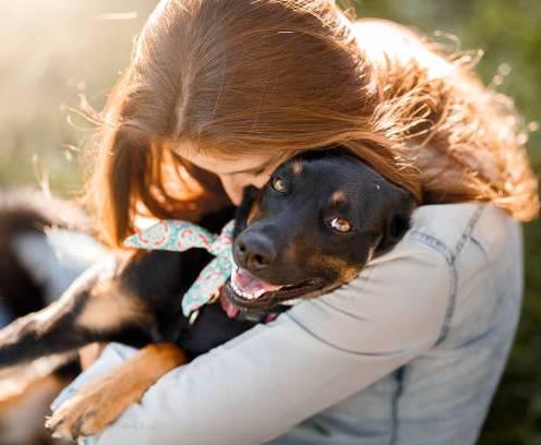 Girl hugging her cute black mutt dog