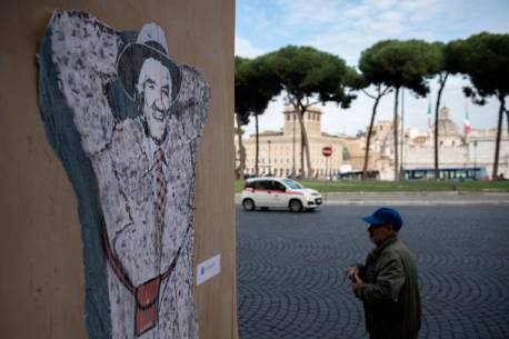 "ROME, ITALY - NOVEMBER 05: People walk by the mural painted by the street artist Laika depicting the Italian actor Gigi Proietti at ""Gran caffè Roma"", location of the film Mandrake, during the day funeral of the Roman actor, on November 5, 2020 in Rome, Italy. The Italian actor Gigi Proietti died on his 80th birthday on November 2. (Photo by Antonio Masiello/Getty Images)"