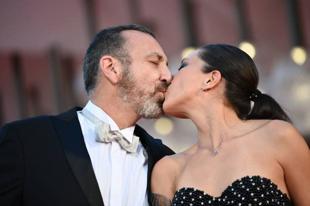 """Mexican actor Hernan Mendoza and his companion kiss as they arrive for the screening of the film """"La Caja"""" (The Box) presented in competition on September 6, 2021 during the 78th Venice Film Festival at Venice Lido. (Photo by Marco BERTORELLO / AFP) (Photo by MARCO BERTORELLO/AFP via Getty Images)"""