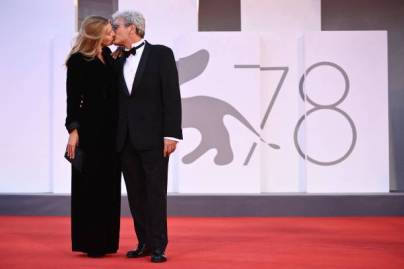 """Italian screenwriter Ippolita Di Majo and her husband Italian director Mario Martone kiss as they arrive for the screening of the film """"Qui Rido Io"""" (The King of Laughter) presented in competition on September 7, 2021 during the 78th Venice Film Festival at Venice Lido. (Photo by Marco BERTORELLO / AFP) (Photo by MARCO BERTORELLO/AFP via Getty Images)"""