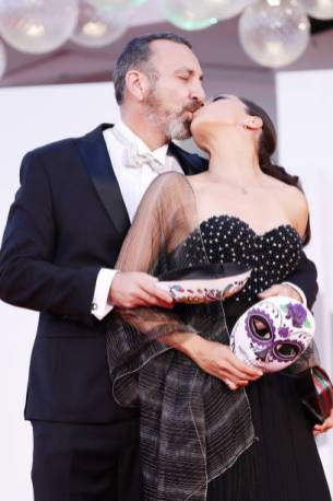 """VENICE, ITALY - SEPTEMBER 06: Hernan Mendoza and a guest share a kiss wearing Mexican death masks on the red carpet of the movie """"La Caja"""" during the 78th Venice International Film Festival on September 06, 2021 in Venice, Italy. (Photo by Vittorio Zunino Celotto/Getty Images)"""