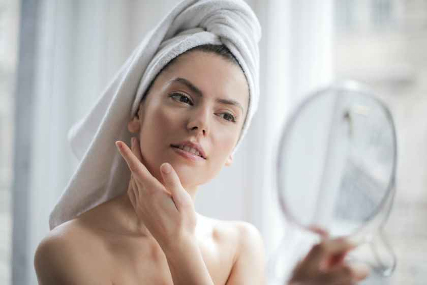 selective focus portrait photo of woman with a towel on head looking in the mirror