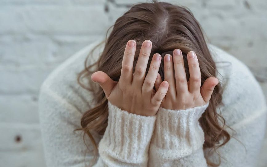 faceless woman covering face with hands while sitting at home
