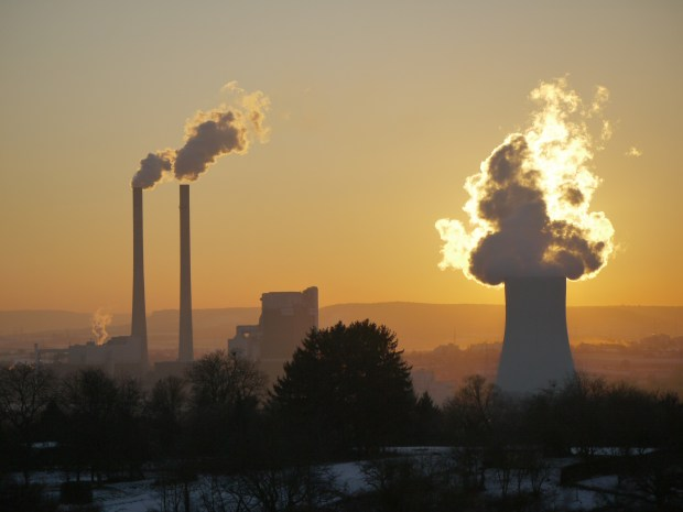Silhouettes of fossil fuel smokestacks in a yellow sunset