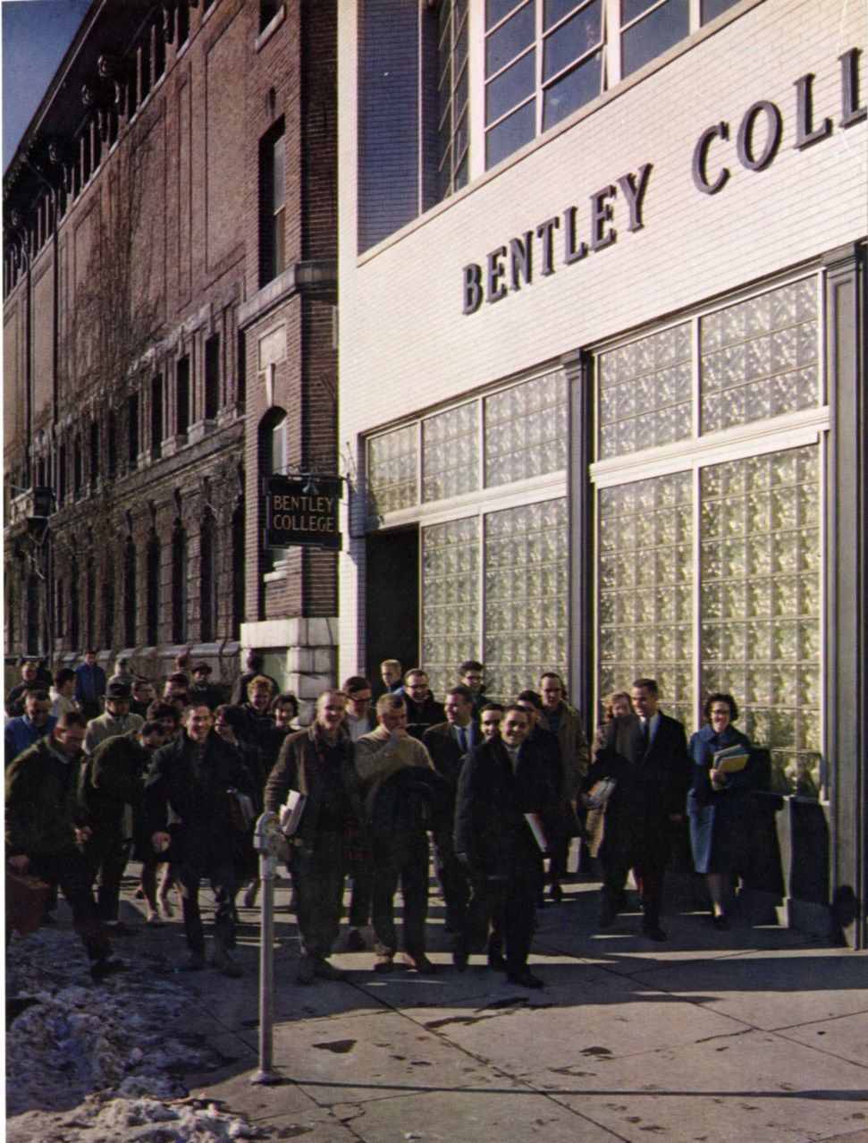 Students walk outside 921 Boylston Street in 1964. Before the move to Waltham, Bentley was primarily a commuter school. Though many students now live on campus, there are still large numbers of commuters whose needs are represented by the Commuter Association.