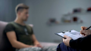 Psicólogo tomando notas durante la sesión de terapia con soldado masculino