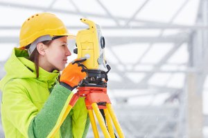Female archaeologist using survey equipment