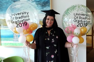 Emma in her graduation gown, holding celebration balloons in both hands.