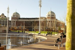 People sat on benches and walking through Centenary Square in Bradford City Centre on a bright and sunny day.