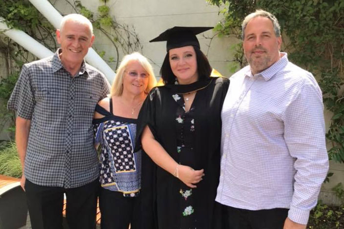 Emma stood with three family members at her graduation.