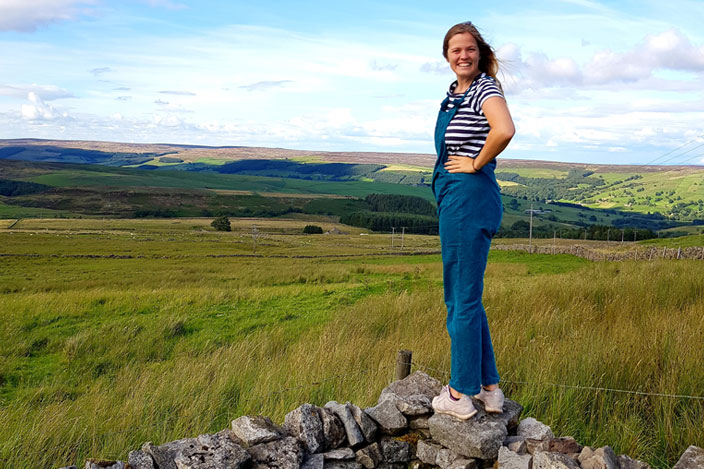 Maria stood on a wall in a field, with hills in the distance.