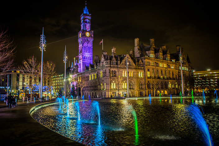 Centenary Square, Bradford city centre, lit up at night with active water displays.