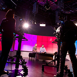 Two students operating cameras and two students sat on set in the University's TV Studio.
