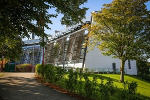 The exterior of the Bright Building on campus, with a path leading up to it, situated between grass areas with trees..