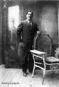 Antonio Longoria stands tall and proud in this photograph, a stately man in a suit.