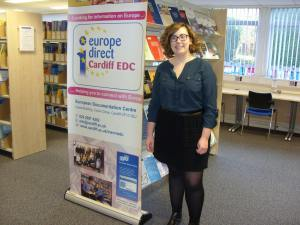 Woman in glasses and shoulder-length hair smiling into the camera. She's standing next to a banner with 'europe direct Cardiff EDC' printed on it.
