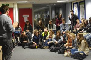 A group of male and female students listening to a male speaker.