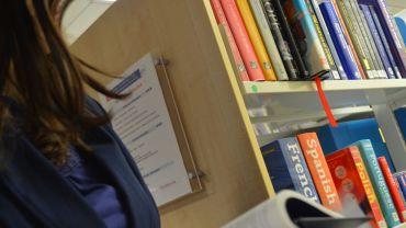 A woman reading a book next to some book shelves