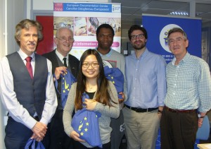 Five men and a woman are smiling at the camera. Three of them are holding bags printed with the Europe Direct logo.