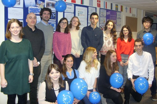 A group pf students, some standing and some kneeling, holding balloons.
