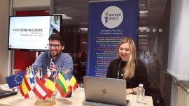 A man and a woman sit at a table with a laptop and an arrangement of European flags. Behind them are a Europe Direct banner and a screen showing 'Fake news in Europe'