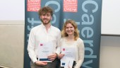 Award winners Josh and Emilia stand side by side holding their certificates in front of Cardiff Uni banners