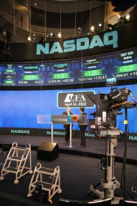 John Rogers, President and CEO of CFA Institute, is briefed by NASDAQ staff before closing the NASDAQ on 12 April 2012.