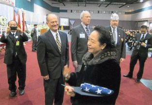 General Vang Pao's wife receiving the American flag at her husband's memorial service.