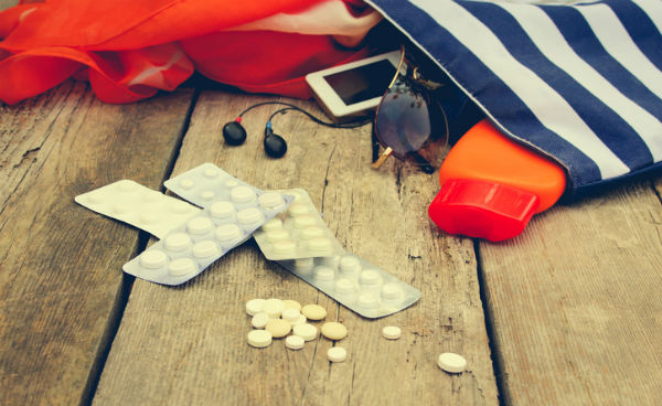 Stripped travel bag on ground with pills resting just outside of it