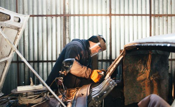 man repairing body of old car