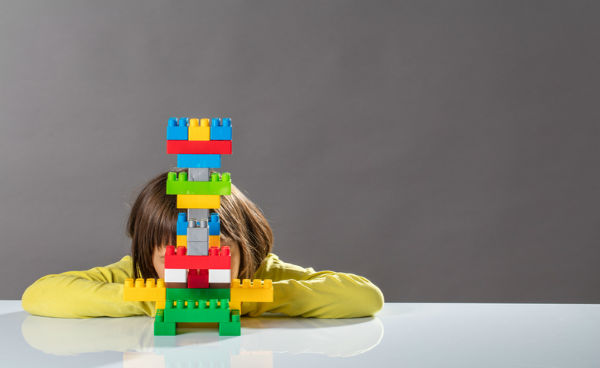 child's face hidden behind colorful toy blocks