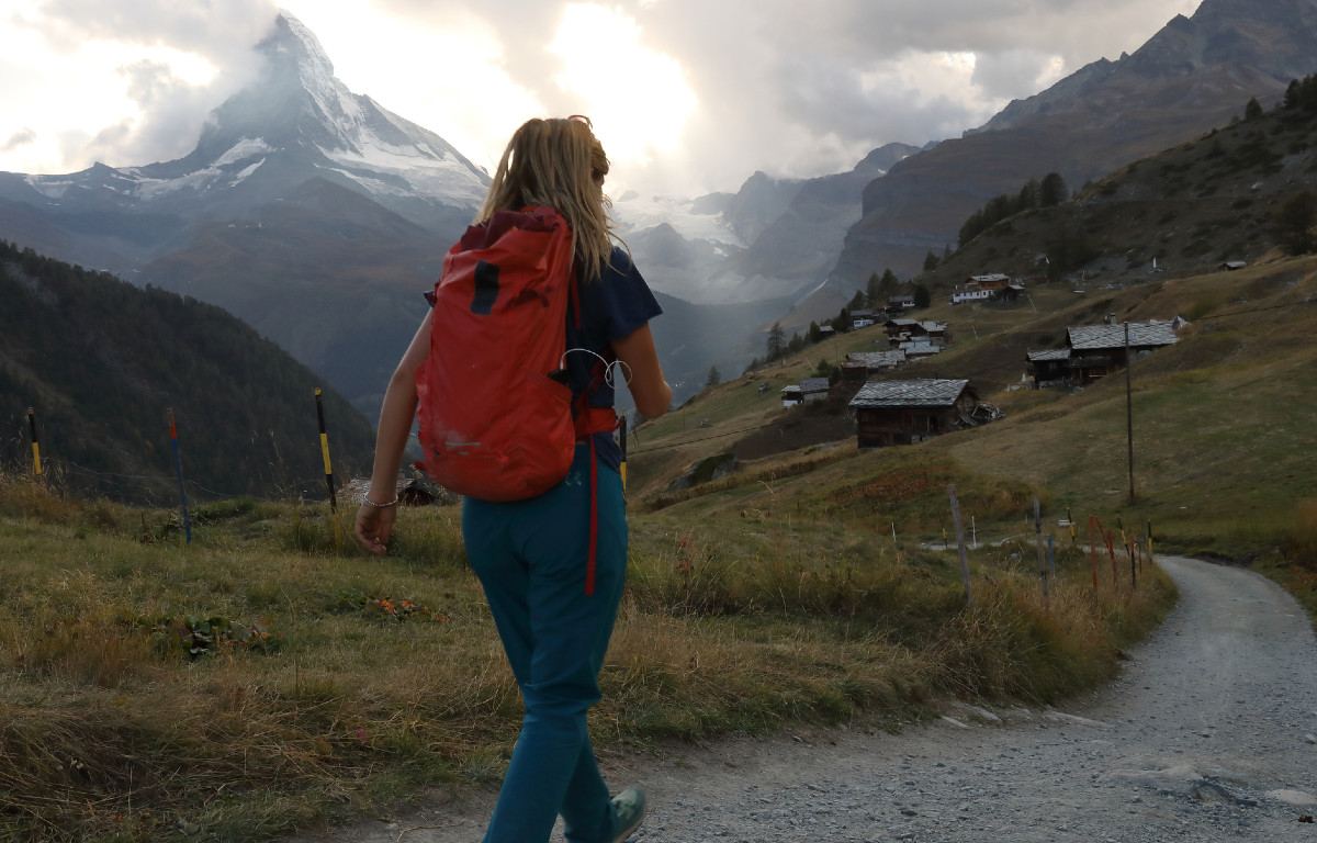 Young woman walking winding road to through small village, mountains in background